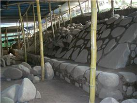 Excavated area with a flat dusty area to the left with some rubble and with steeply sloping well-dressed stonework to the right sat on top of a low vertical stonework base. A ramshackle roof protecting the excavations is supported by wooden poles.