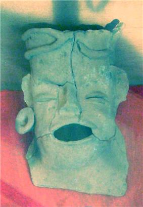 A cracked ceramic head with open mouth and closed eyes. The left ear sports an earplug. The forehead is heightened and flattened at the top.
