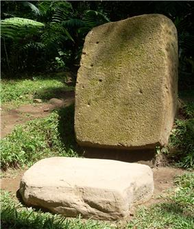 A moss-covered upright stone slab, fallen slightly from vertical. The slab has a number of small cup-like depressions in the surface. In front of it is a horizontal roughly square slab of pale stone with faint designs sculpted around the edges.