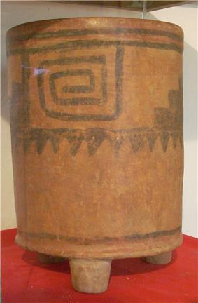 A tall cylindrical ceramic vessel with three stubby legs. The base colour is orange with a darker pattern consisting of a square spiral.