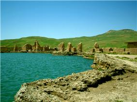Ruins of buildings near a lake.
