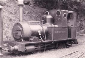 A small steam locomotive stands beside a banked area. On the left hand coal bunker is painted TAL-Y-LLYN RAILWAY. The track is covered with grass, and the rails are barely visible. In the foreground are some disused rails.
