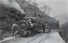 A train consisting of a locomotive and single carriage stands in the centre track of three tracks, which is on a ledge on a steep hillside. There is no platform. Two adults and two girls in Victorian dress stand on the track beside the carriage, with a man leaning against the locomotive and another man on the footplate.