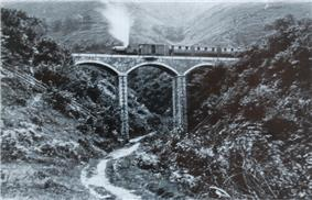 A stone viaduct with three arches spans a steep sided ravine. A steam train stands on the viaduct, with an engine, a van and three coaches.
