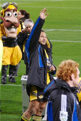 A Polynesian man wearing a yellow rugby jersey and a black jacket with his arm raised