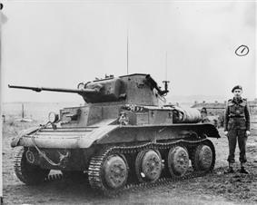A small, squat tank sits in a field, its left-hand tracks facing the camera. Its gun barrel has been lengthened with a metal extension. A man in uniform with a black beret stands next to it. In the background, fields can be seen to the left, and several houses to the right.