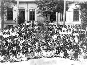 A black-and-white photograph of several dozen girls seated in front of a school building