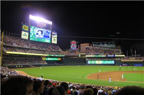 Baseball field at night, scoreboard displays a player, Twins