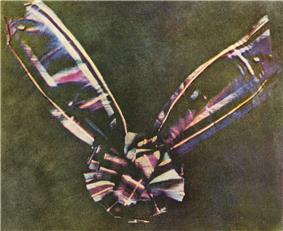 A bow made of tartan ribbon.  The center of the bow is round, made of piled loops of ribbon, with two pieces of ribbon attached underneath, one extending at an angle to the upper left corner of the photograph and another extending to the upper right.  The tartan colors are faded, in shades mostly of blue, pink, maroon and white; the bow is set against a background of mottled olive.