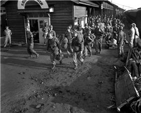 Soldiers carrying their bags off of a train in Daejeon train station, South Korea