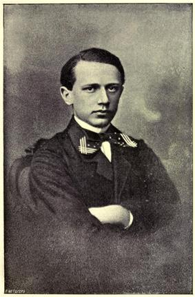 A clean-shaven man in his teens wearing a dress shirt, tie and dark uniform jacket.