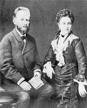 A middle aged man with dark hair and a beard, wearing a dark suit and holding a book, sits next to a young woman in a black dress wearing her hair up on her head