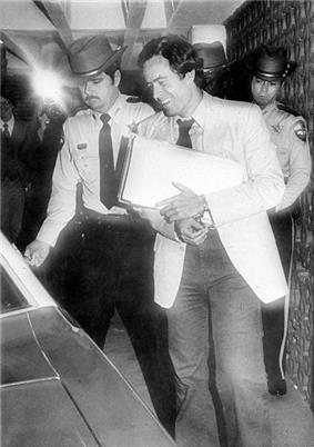 A smiling Bundy holds a sheaf of papers and enters a vehicle. He is escorted by two police officers.