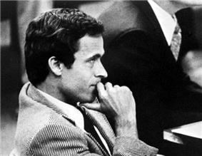 Bundy is seen from the side. He is wearing a striped business suit and has his hand positioned near his chin.