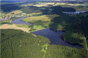An aerial view showing several dammed lakes within a forested and urban landscape