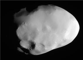 A potato shaped body is illuminated from the right. The terminator runs from the top to bottom. There is a large crater at the bottom near the terminator. The body is elongated from the right to left.