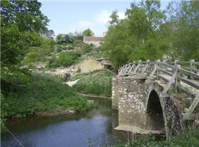Stone arched bridge with wooden handrail over river.