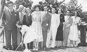 A line of men and women in suits and dresses respectively, standing outside beside a large American flag on a pole. In front of them, a young girl holds a shovel dug into the ground.