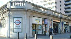 A grey building with a rectangular, white sign on a rounded corner reading