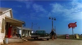 A flat, rural setting under a vast sky. On the left, a man sits on the porch of a small, old wooden building. In front of him, another man stands beside a pickup truck parked next to a gas station pump. On the right, a tall red sign reads