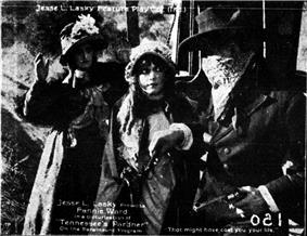 A masked man with a gun looks at two women in front of him