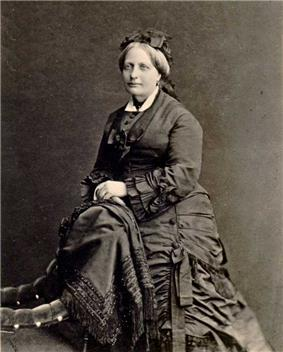 A photographic portrait of a woman with graying hair dressed in an elaborate dark mid-Victorian period dress and leaning against the back of an upholstered chair