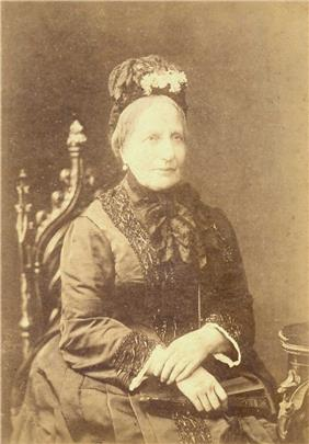 A photographic portrait of a seated woman with graying hair who is dressed in a dark and elaborate late-Victorian style dress and wearing a flowered bonnet
