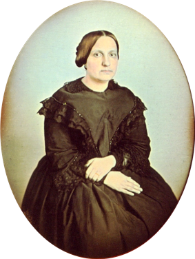 Photographic portrait of a woman seated and wearing a dark dress trimmed in dark lace, with her hair pulled back into a bun and no jewelry except for a simple ring on her left hand