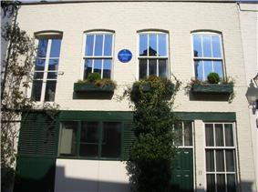 exterior of cream painted mews house, with blue plaque on front wall