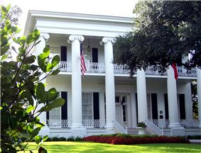 A white Greek-revival-style mansion with 6 tall columns visible at the front and two stories