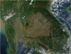 A view of Southeast Asia (Myanmar, Thailand, Laos, Cambodia, Vietnam, and southern China) from space, showing a large, central brown patch in the area of Thailand.