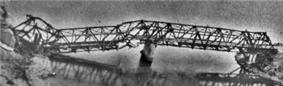 Wide, black and white view of Thanh Hóa Bridge badly damaged. The left support column has collapsed.