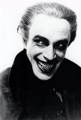 A young man looks away from the camera with a stretched-wide smile