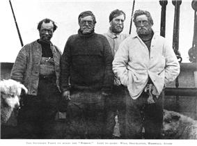 Four menwearing dishevelled clothing and worn expressions face the camera. The head of a dog is just visible on the left.