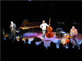 Stage with three musicians in their thirties. Left to right, man in a suit next to a Steinway grand piano, man in jeans holding a bass fiddle, man in jeans playing drums. Heads of audience visible in front.