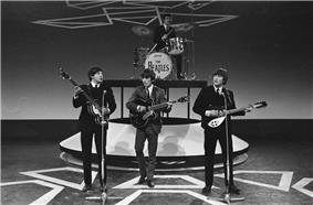 Monochrome image of The Beatles performing on a stage wearing dark suits.