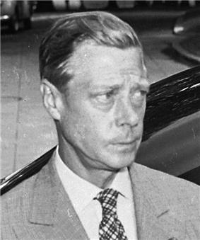 A middle-aged man with fair hair, wearing a light-coloured jacket and cross-striped tie, looks to the right with a furrowed brow and pursed lips.