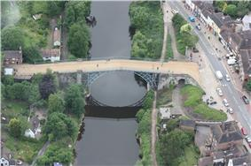 An aerial photo of the bridge, showing the close proximity of the main road alongside the river and the many building dotted nearby.
