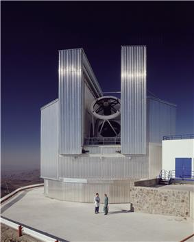 Large metallic telescope, with two people in front giving an idea of its size