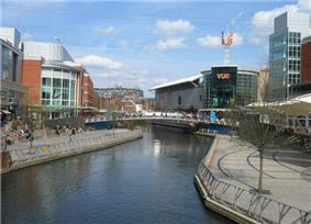 Stretch of canal with large modern buildings and concrete walkways on either side.