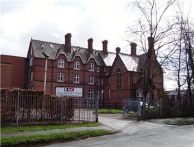 A large brick building with a sign saying