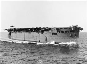 Black and white photograph of an aircraft carrier at sea. An aircraft is about to land on her stern, and another aircraft is positioned at the forward end of the flight deck