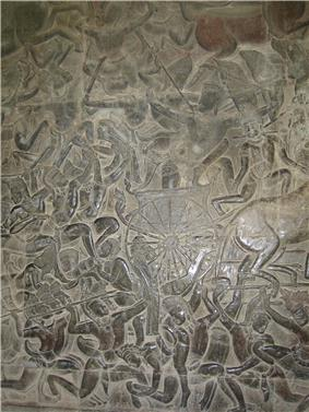 A black stone relief depicting a number of men wearing a crown and a dhoti, fighting with spears, swords and bows. A chariot with half the horse out of the frame is seen in the middle.