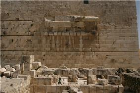 slightly curved blocks form the spring of an arch in the middle of a wall of otherwise flat-faced stones