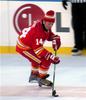 A hockey player in a red uniform with white and yellow trim.  He is focused on the ice surface, as he attempts to control a puck while skating