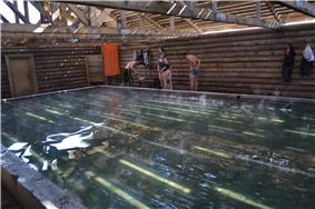 Interior of a wooden structure containing a spa pool, with people
