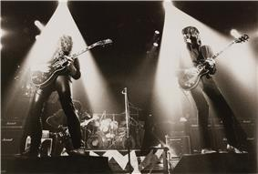 Two guitarists perform onstage with spotlights on them