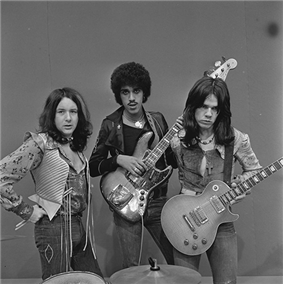 The band pose with their instruments for a black-and-white photo and look to the camera
