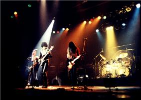 The band performing onstage with multi-coloured lights shining on them