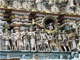 A sculpture depicting a person is a palanquin carried by others.